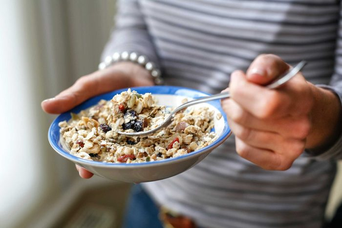 woman with bowl of cereal with berries, taking a spoonful