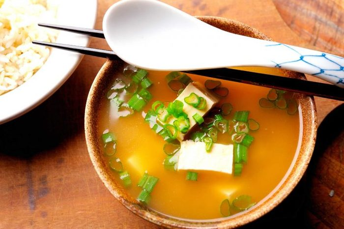 Bowl of miso soup with tofu and green onions.
