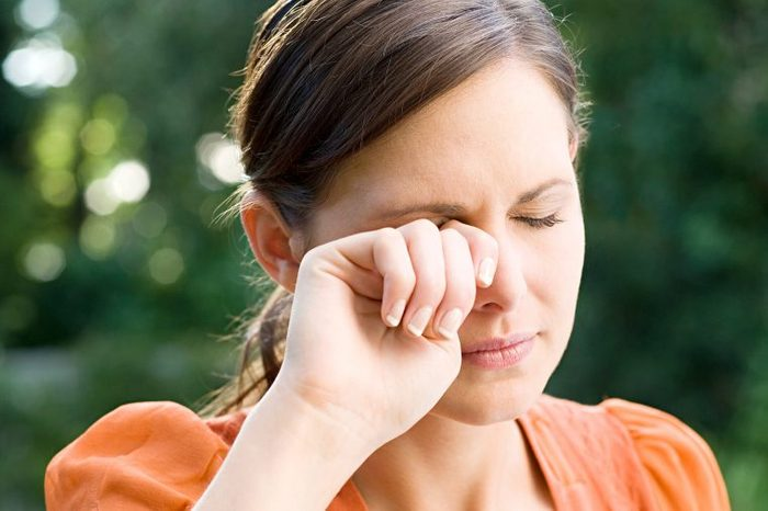 Woman standing outside wiping at her eye with her right hand.