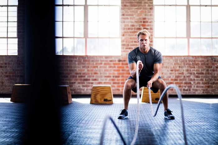 young man working out with ropes in a gym
