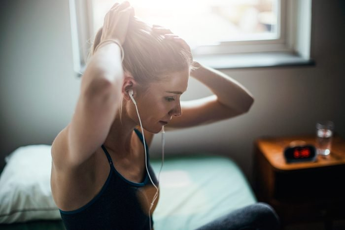 woman in workout gear with earbuds