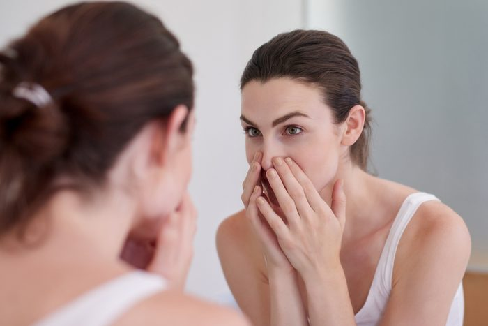 woman closely looking at face in mirror