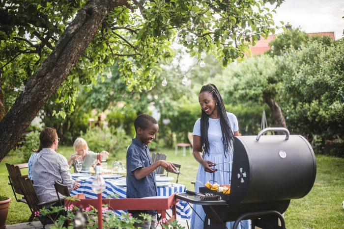 mother and son grilling food for barbecue with family