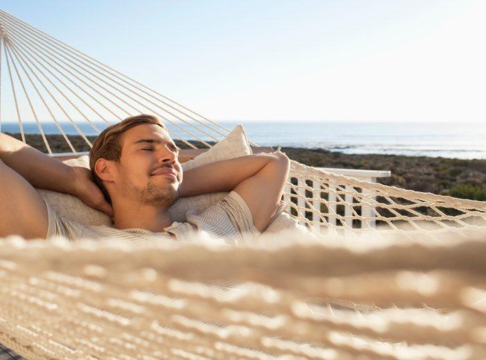 man laying in a hammock in the sun