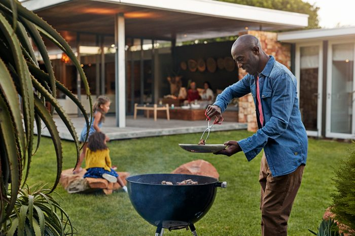 man grilling in his backyard with family