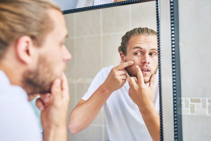 man squeezing pimple in mirror