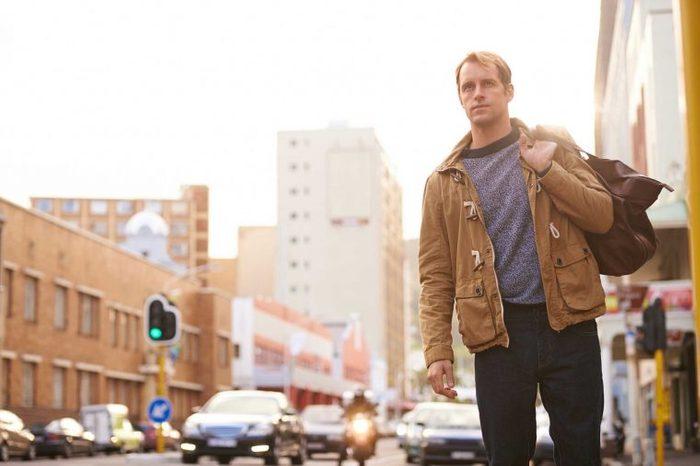 Man walking down a street wearing a jacket.
