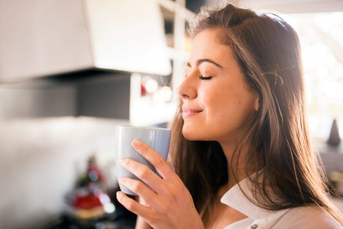 woman smiling and holding a cup of coffee