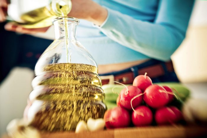 person pouring olive oil in decanter