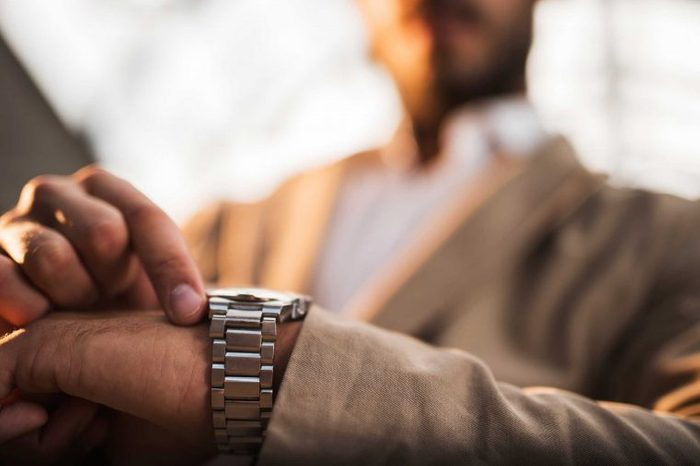 Man looking at a silver watch on his wrist.