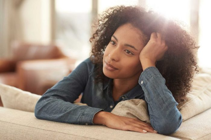 A woman in a denim shirt leaning on the back of a couch.