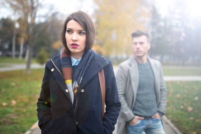 Woman in a coat walking in a park in front of a man.