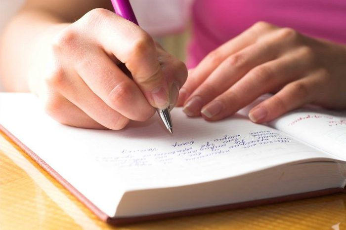 Woman in a pink top writing in a journal with a pen.