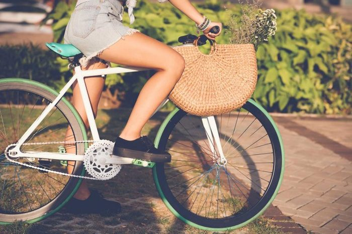 Woman with a purse pedaling on her bike outdoors.