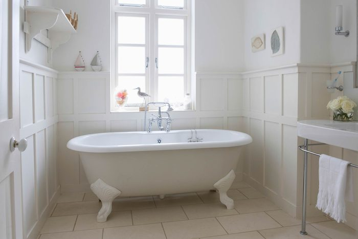 white clawfoot tub in a white sunny bathroom