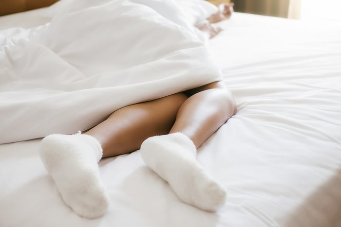 close up of woman's socks while laying in bed