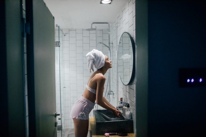 woman in the bathroom at night after taking a shower
