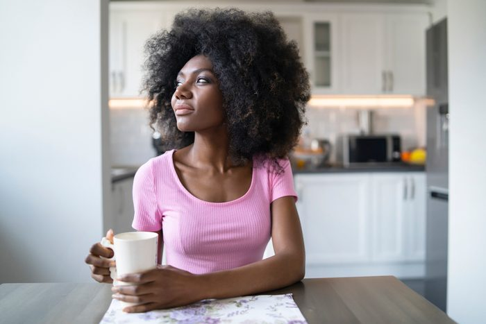 woman sitting at table at home looking away from camera