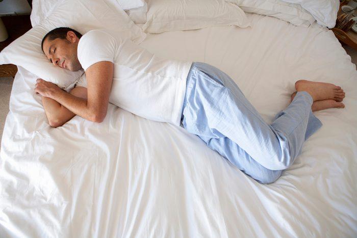 man sleeping on bed with long pajama pants on