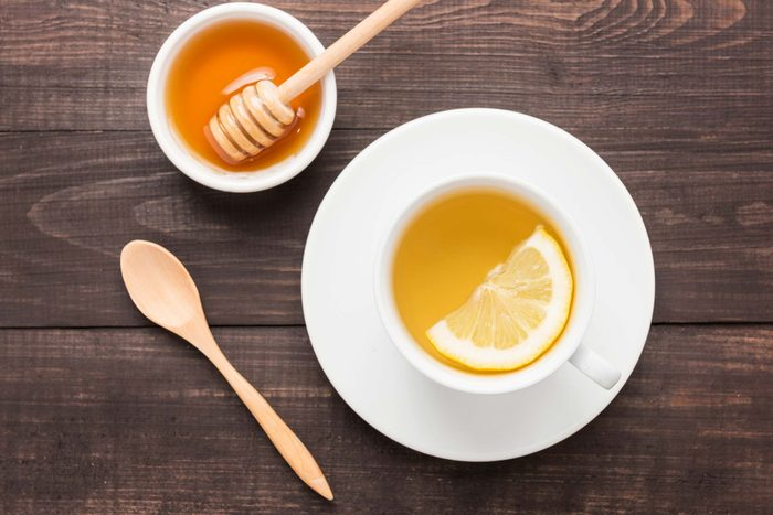 cup of tea with lemon and bowl of honey