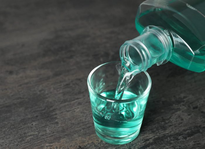 Pouring mouthwash in glass and space for text on dark background. Teeth care