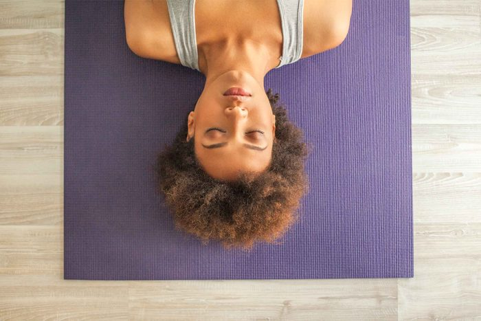 woman on yoga mat with eyes closed