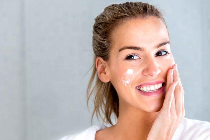 smiling woman applying face cream