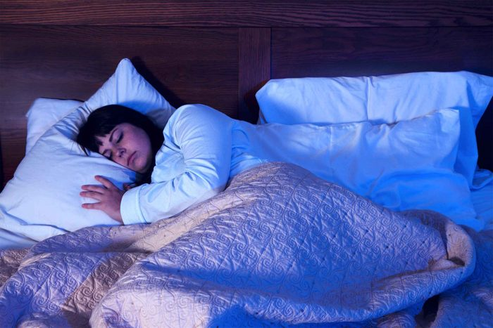 woman in cozy bed in dark room with pillows