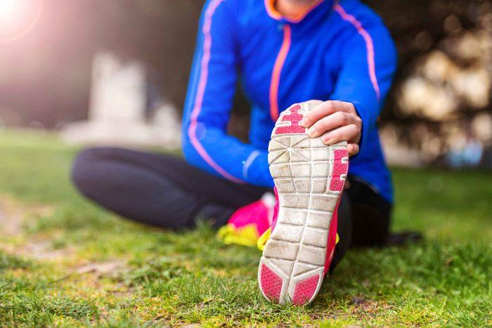 runner doing stretch on ground holding sneaker