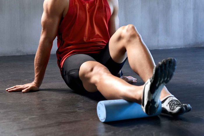 man in gym clothes using foam roller