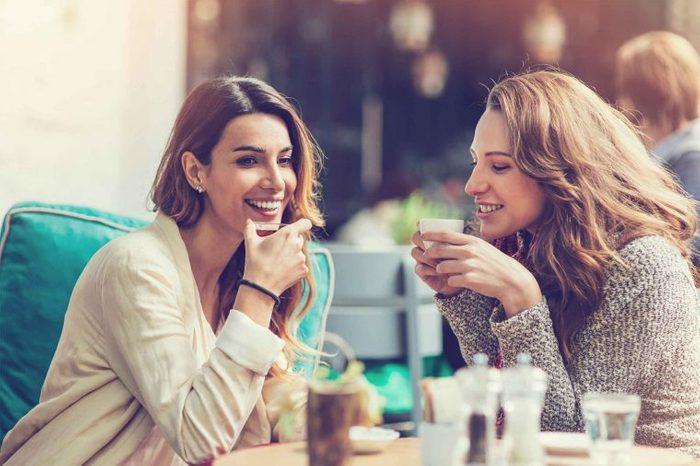 Two women talking in an outdoor cafe.