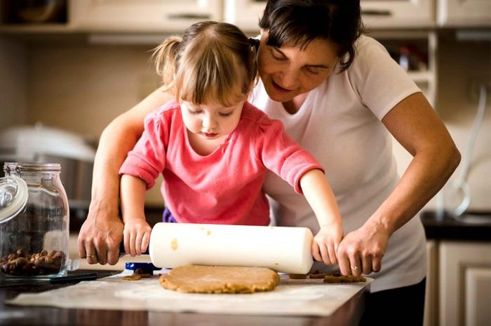 Mother and daughter rolling out dough with a rolling pin in the kitchen.
