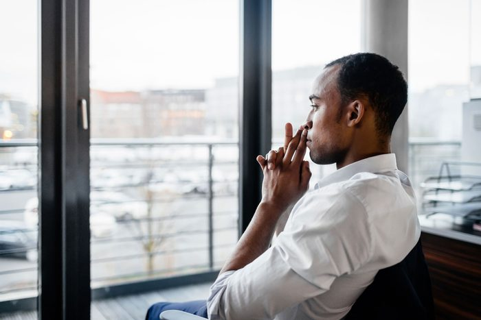 man sitting in chair looking out window