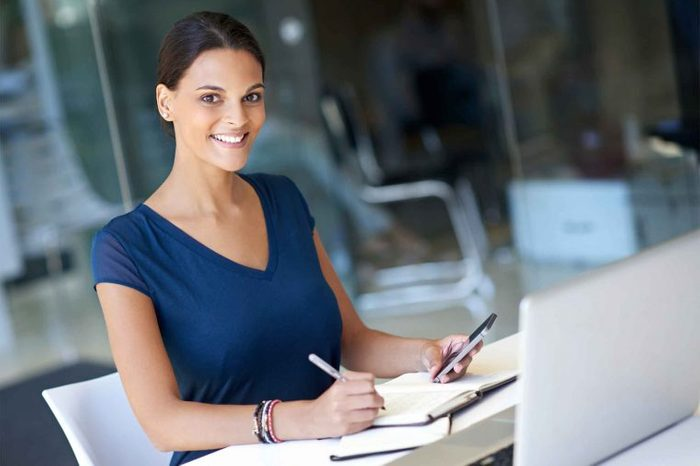 Woman in a blue shirt sitting at a desk writing in a journal.