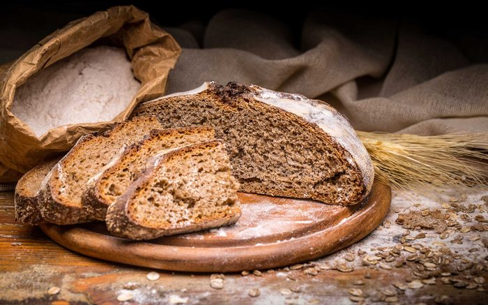 dark brown bread on board with bag of flour