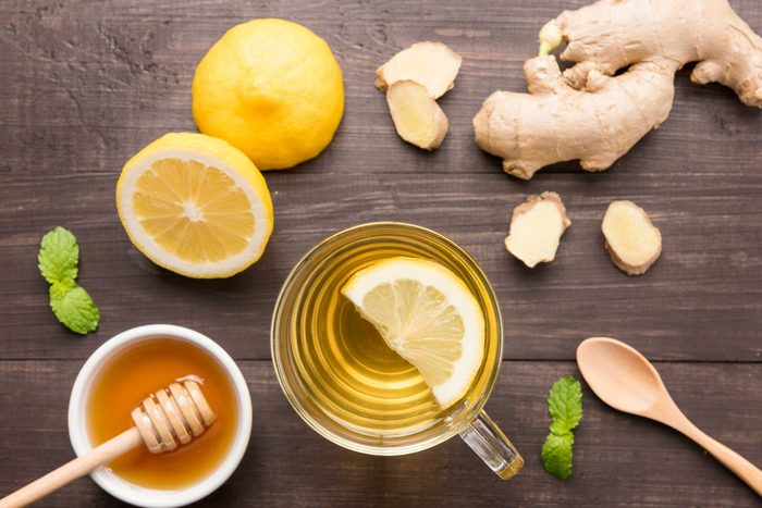 mug of tea with lemon surrounded by lemon, ginger, honey, and mint