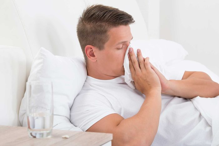 Man blowing his nose with a tissue in bed.