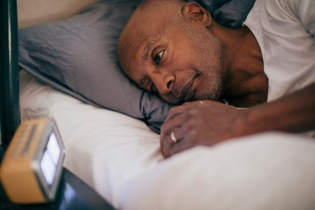 man laying awake in bed at night unable to sleep
