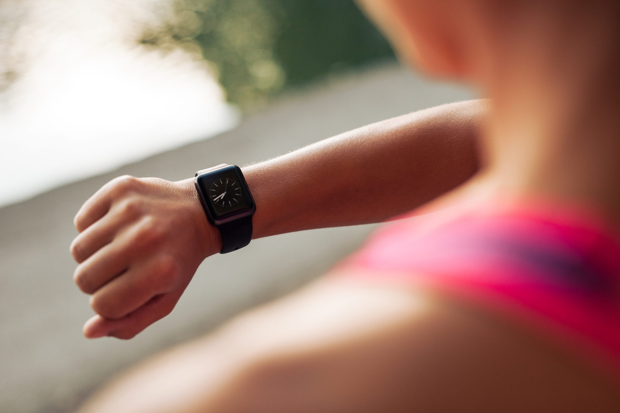 woman checking time on watch while exercising