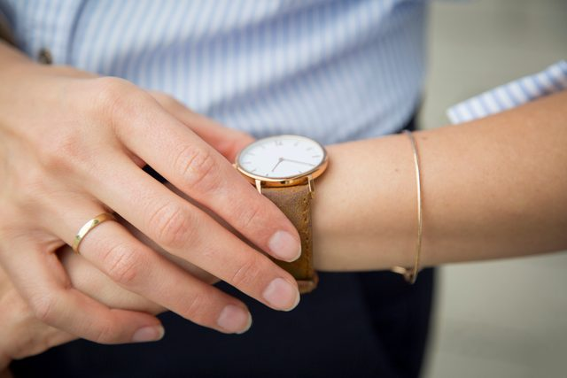 close up of woman checking the time on her wrist watch