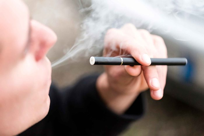 person exhaling vapor from e-cigarette