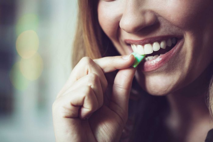 smiling woman putting a piece of gum in her mouth