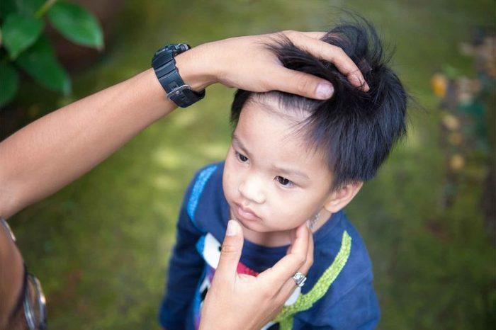 Parent checking a little boy's hair and throat.