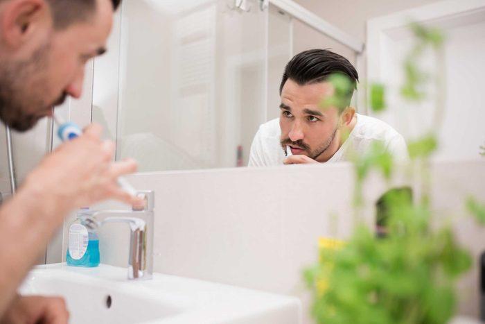 man brushing teeth and looking in mirror