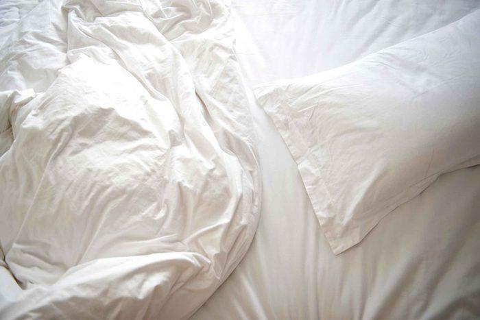 wrinkled white bedsheets