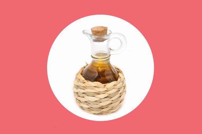 apple cider vinegar in a straw-bottomed glass pourer