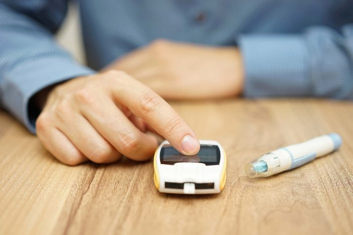 Man using a glucometer to check his blood sugar.