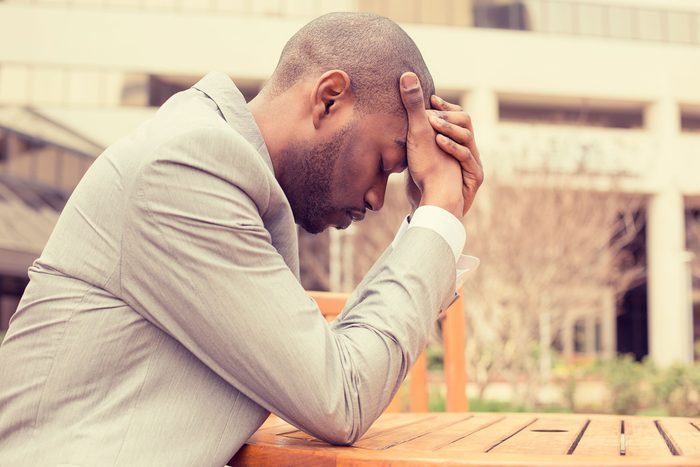 Black man sitting outdoors at a table, holding his head with his eyes closed