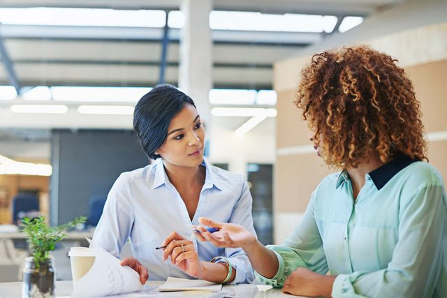 two woman talking at work