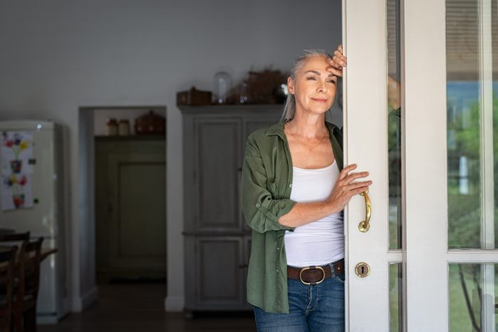 woman standing at home entrance looking outside